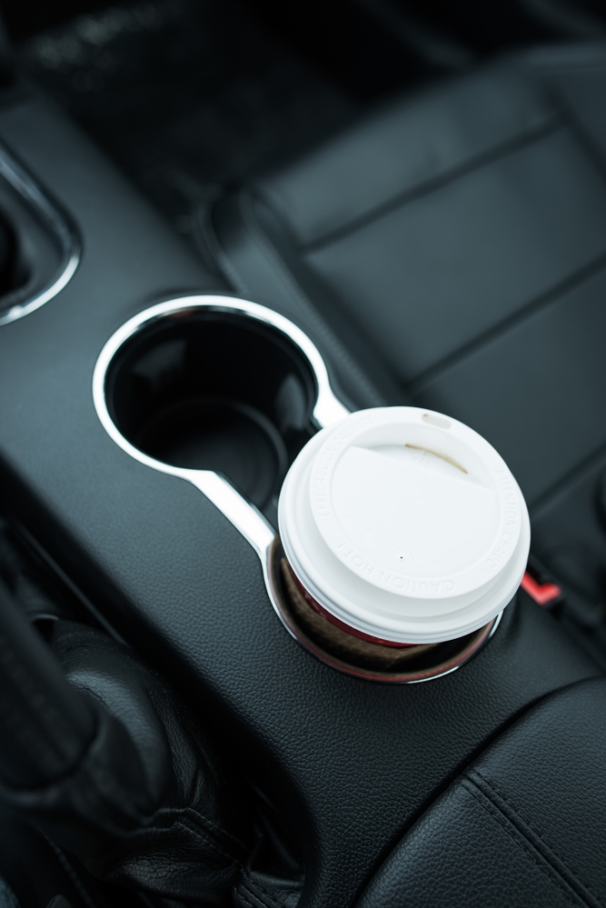 Coffee Drinking While Driving. Single Paper Coffee Cup Inside Car Cup Holder.